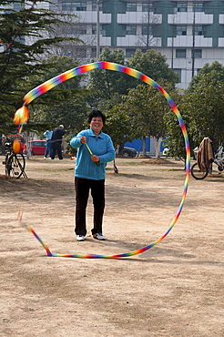 China, Jiangsu, Nanjing, Woman in a blue sweater and sneekers relaxing in a municipal park spinning a top with a multicoloured tail with an apartment block in the background.