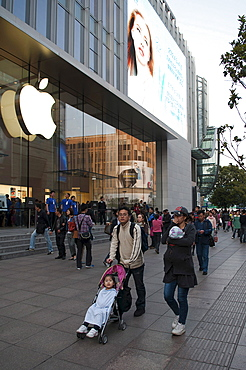 China, Shanghai, Modern young Chinese family with daughter in stroller and infant in sling stroll past the Apple store on Nanjing Lu Store staff and Security on steps at entrance evening light
