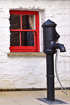 Ireland, North, Derry, Craft Village, Old water pump with small red window in background.