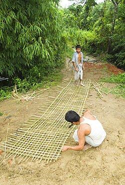 Bangladesh, Chittagong Division, Khagrachari, Two men weaving a large bamboo fence panel.