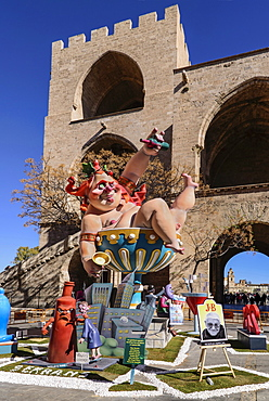 Spain, Valencia Province, Valencia, Grotesque Papier Mache figure at the Serranos Towers during Las Fallas festival.