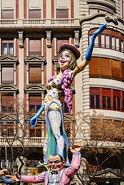 Spain, Valencia Province, Valencia, Papier Mache figure of a woman standing on another figures shoulders in the street during Las Fallas festival.