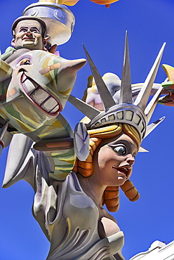 Spain, Valencia Province, Valencia, Papier Mache figure of a woman resembling the Statue of Liberty with another figure flying around her during Las Fallas festival.