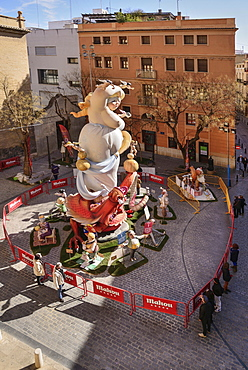 Spain, Valencia Province, Valencia, Papier Mache falla scene with onlookers viewing a giant figure of a lady in the street at Torres de Quart during Las Fallas festival.
