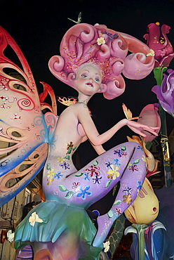 Spain, Valencia Province, Valencia, Papier Mache figure in the street at night during Las Fallas festival.
