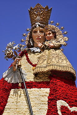 Spain, Valencia Province, Valencia, Statue of Virgen de los Desamparados, Our Lady of the Forsaken, decked out with flowers carried in the religious procession during Las Fallas festival.