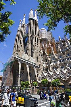 Spain, Catalonia, Barcelona, Tourists viewing the basilica church of Sagrada Familia deisigned by Antoni Gaudi in the Eixample district.