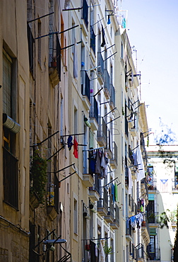 Spain, Catalonia, Barcelona, Washing hanging from windows of an apartment building in the Gothic Quarter district.