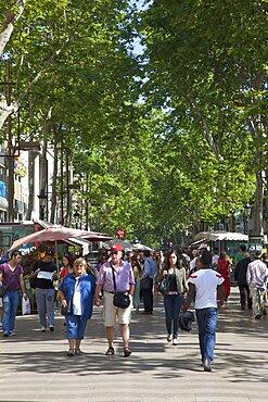 Spain, Catalonia, Barcelona, Tourists walking along the tree lined avenue of La Rambla.