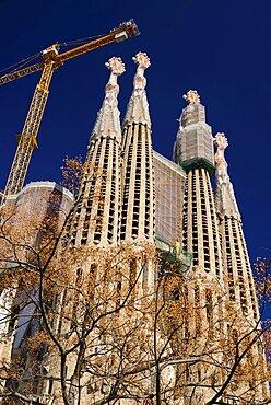 Spain, Catalonia, Barcelona, Basilica i Temple Expiatori de la Sagrada Familia, Generally known as Sagrada Familia, General view of the Passion Facade with crane hanging above.