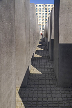 Germany, Berlin, A tourist walking through The Memorial to the Murdered Jews of Europe more commonly known as the Holocaust Memorial.