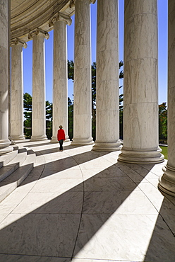 USA, Washington DC, National Mall, Thomas Jefferson Memorial, A tourist strolls among the Ionic columns with long shadows cast by evening sun.
