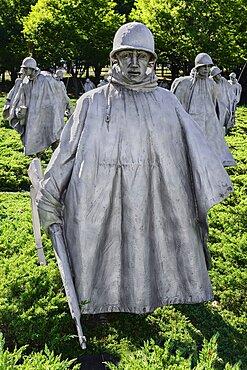 USA, Washington DC, National Mall, Korean War Veterans Memorial, Statues of soldiers on patrol in combat gear among juniper bushes.