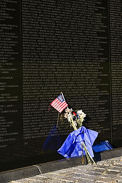 USA, Washington DC, National Mall, Vietnam Veterans Memorial, A section of The Memorial Wall with the names of those killed or missing in action during the Vietnam War, Bunch of flowers and American flag resting against the wall.