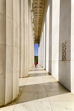USA, Washington DC, National Mall, Lincoln Memorial, A tourist strolling among the Doric columns of the peristyle surrounding the memorial.