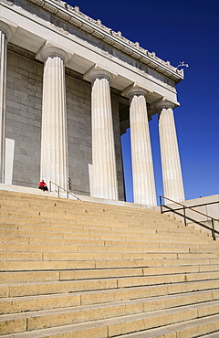 USA, Washington DC, National Mall, Lincoln Memorial, A tourist sitting among the Doric columns of the peristyle surrounding the memorial.