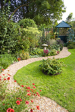English cottage garden, winding shingle path leading to a gazebo between grass lawn and flowerbed of mixed plant varieties.