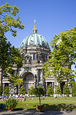 Germany, Berlin, Mitte, Museum Island. Berliner Dom, Berlin Cathedral, with green copper domes and people on the grass in Lustgarten.
