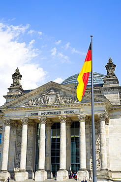 Germany, Berlin, Mitte, The Reichstag building in Tiergarten with the inscrption Dem Deucschen Volke, For the German People, on the facade above the columns at the entrance with a German flag on a flagpole and Norman Foster's glass roof dome behind.