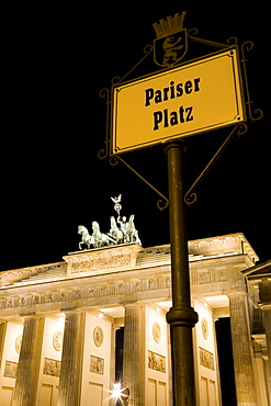 Germany, Berlin, Mitte, Brandenburg Gate or Brandenburger Tor and roadsign for Pariser Platz illuminated at night leading to Unter den Linden and the Royal Palaces with the Quadriga of Victory on top. The only remaining of the original 18 gates in the Berlin Customs Wall.