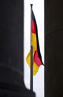 Germany, Berlin, Mitte, a black, red and yellow national flag hanging down from a flagpole outside the Reichstag building in Tiergarten.