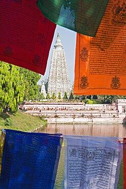 India, Bihar, Bodhgaya, Mahabodhi Temple framed by colourful Buddhist prayer flags.