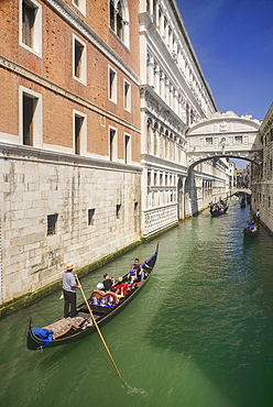 Italy, Venice, Doge's Palace and Bridge of Sighs with gondolas passing.