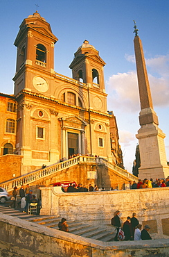 ITALY Lazio Rome Trinita dei Monti sixteenth century church at the top of the Spanish Steps at sunset with tourist crowds.
