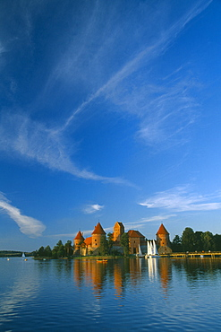 LITHUANIA  Trakai Wide angle view of castle reflected in lake with windswept clouds above
