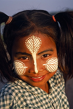 MYANMAR  Amarapura Head and shoulders portrait of young girl at U Bein Bridge near Mandalay wearing thanakha paste patterns on her face to beautify and protect skin from the sun. cosmetic made from tree bark. Burma