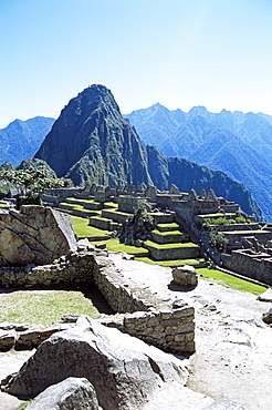 PERU Cusco Department Machu Picchu Inca ruins and Huayna Picchu  wall in foreground. Cuzco Travel Tourism Holiday Vacation Explore Recreation Leisure Sightseeing Tourist Attraction Tour Destination Machu Picchu Machupicchu Huayna Wayna Peru Peruvian South Southern America Culture Cultural Tranquil Tranquility Sacred Valley Of The Inca Incas Inka Inkas Incan Hill Hillside Trail Mountain Mountainous Mountainside Overlooking Overlook Scenic Landscape View Vista Picturesque Dominant Dominating Prominent Andes Andean Ruins Remains Ancient Civilisation Civilization Peak High Tall Range Altitude Architecture Architectural Archaeology Archaeological UNESCO World Heritage Site Old Historic Peaceful Landmark Vast Citadel Panorama Panoramic Spiritual Lost City Remote Spectacular Magnificent Beautiful Secluded Seclusion Isolated Wall Calendar American Cusco South America