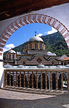 BULGARIA  Rila Nativity Church from balcony through arch  Rila Monastery. Travel Tourism Holiday Vacation Explore Recreation Leisure Sightseeing Tourist Attraction Tour History Historic Historical Nativity Church Religion Religious Building Architecture Architectural Tranquility Tranquil Calm Peaceful Christianity Orthodox Holy Divine Christian Theology Pray Prayer Worship Worshipping Worshiping Faith Bulgaria Bulgarian East Eastern Europe European Calendar Vivid Vibrant Rila Monastery Monastic Ornate Intricate UNESCO World Heritage Site Rilski Museum Summer Bright Sunny Sun Monument National Arches Arch Arched Balcony Blue Sky Stripes Stripe Striped Symmetry Symmetrical Graphic Banister Dome Frame Framed Framing Eastern Europe