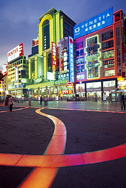 CHINA  Shanghai Nanjing Lu.  Busy street scene at night with illuminated neon signs and advertising and ribbon of pink / orange lit pavement across square in the foreground.