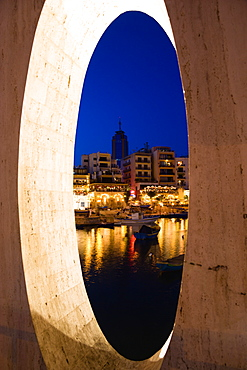 Saint Julians Bay waterfront at dusk with illuminated restaurants in front of apartments and the Hilton Tower office complex with fishing boats in the harbour in the foreground seen through a spherical opening, Saint Julians, Malta