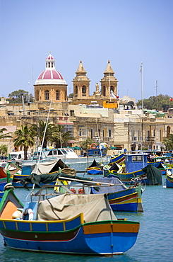 Fishing village harbour on the south coast with colourful Kajjiki fishing boats and the Church dedicated to Our Lady of the Rosary The Madonna of Pompeii, Marsaxlokk, Malta