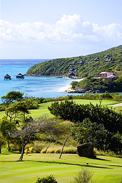 Raffles Resort Trump International Golf Course designed by Jim Fazio, The 7th fairway and 6th green with the pink Villa Juliet and Amrita Spa beyond on Godahl beach, Canouan, St Vincent & The Grenadines