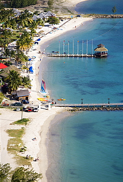 The coconut palm tree lined beach at Sandals Grande St Lucian Spa and Beach Resort hotel with tourists walking swimming or sunbathing, Gros Islet, St Lucia