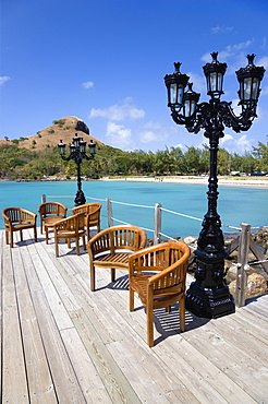 Signal Hill on Pigeon Island National Historic Park seen from a nearby wooden jetty with a table and chairs beside a wrought iron lamppost, Gros Islet, St Lucia