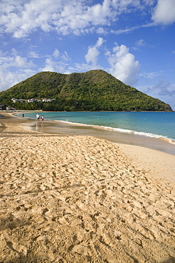 Reduit Beach in Rodney Bay during the early morning with tourists walking by the waterline, Gros Islet, St Lucia