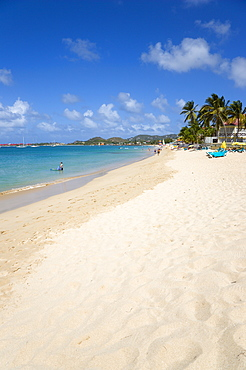 Reduit Beach in Rodney Bay with tourists in the water and on the beach with yachts at anchor in the bay, Gros Islet, St Lucia