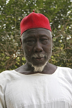 Tanji Village, Head and shoulders portrait of Muslim man with white trimmed beard wearing white shirt and red cap, Tanji, Western Gambia, The Gambia