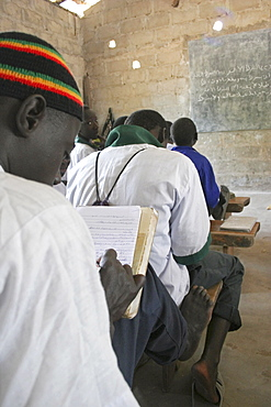 Tanji Village, Muslim boys writing in arabic at their desks while attending an islamic religious class at the Ousman Bun Afan Islamic school, Blackboard on wall in front of them, Tanji, Western Gambia, The Gambia