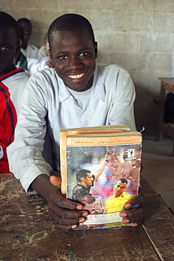 Tanji village, Smiling student from Usman Bun Afan private Islamic school proudly showing his exercise book with picture of a football referee showing a yellow card to Brazilian football player Cafu, Tanji, Western Gambia, The Gambia