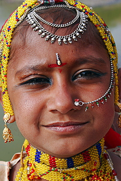 Portrait of a young Indian girl at Meherangarh Fort wearing nose ring and chain and traditional bead jewelery and black kohl eyeliner, Jodhpur, Rajasthan, India