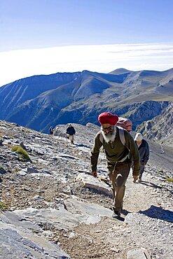 Olympus, Group of four climbing steep slope of Mount Olympus towards the highest peak called Mytikas, Pieria, Macedonia, Greece