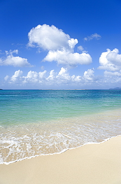 The calm clear blue water breaking on Paradise Beach in LEsterre Bay with Sandy Island in the distance, Grenada, West Indies, Caribbean, Central America