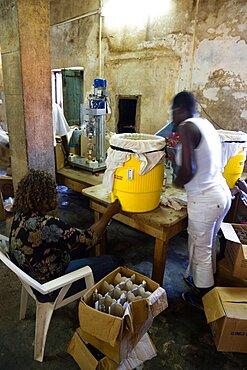 Female workers hand bottling the rum at the River Antoine distillery, Caribbean