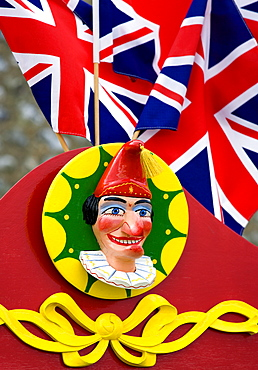 Findon village Sheep Fair Bright red Punch and Judy stand with Union Jack flags and a carved image of Punch, United Kingdom