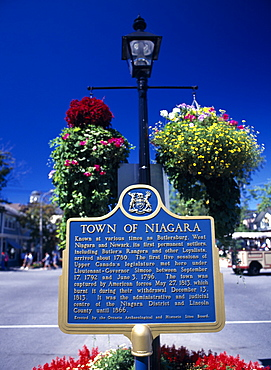 Canada, Ontario, Niagara on the Lake, Queen Street Plaque and hanging baskets.
