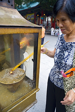 Chinese woman is lighting a candle as an offering outside of Sik Sik Yuen Wong Tai Sin temple